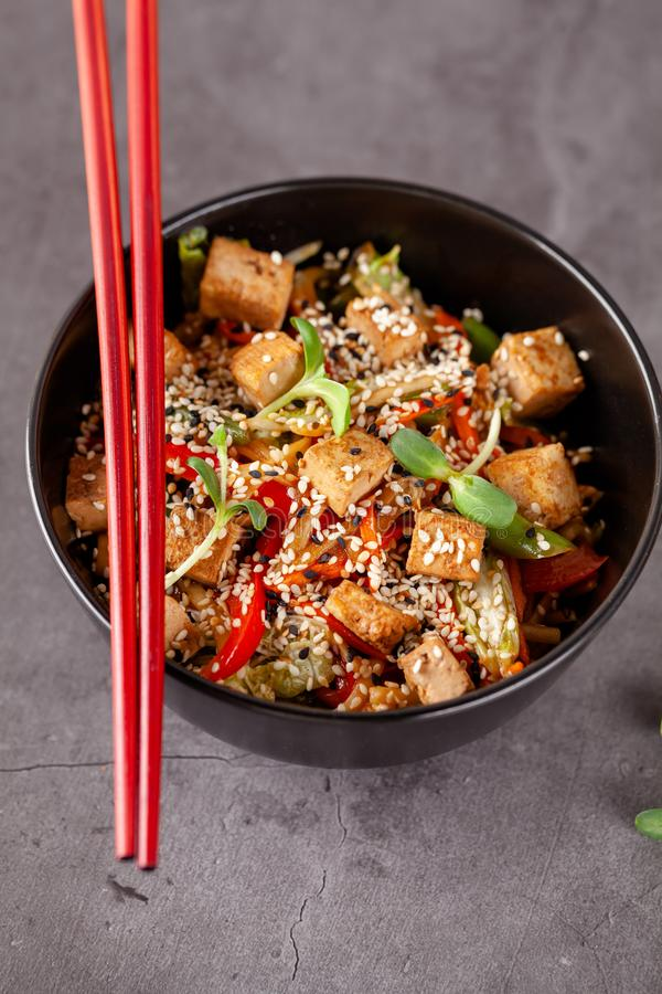 The concept of Japanese cuisine. Vegetarian noodles with tofu cheese and vegetables in a black ceramic plate. Red Chinese sticks. Copy space royalty free stock images