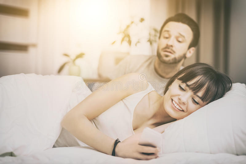 The concept of jealousy and distrust. A young couple lying in bed. One of them use the phone and flirting. The other person is jealous and spies of the arm. The royalty free stock images