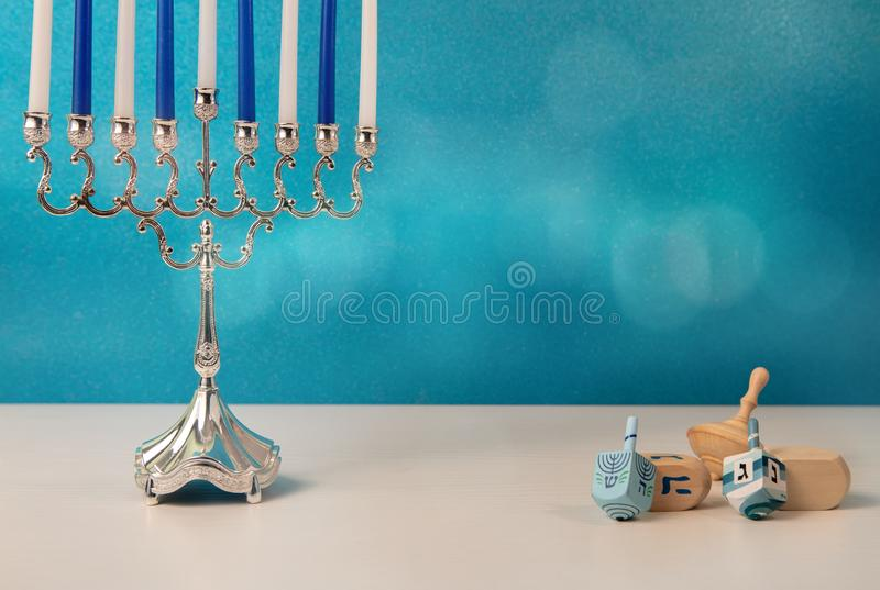 concept of of jewish holiday hanukkah with wooden spinning top toys dreidel and traditional chandelier menorah and candles stock image