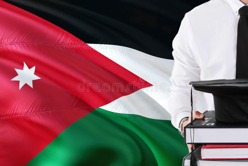 Concept jordanien réussi d'éducation d'étudiant Tenir les livres et le chapeau d'obtention du diplôme au-dessus du fond de drapea photo libre de droits