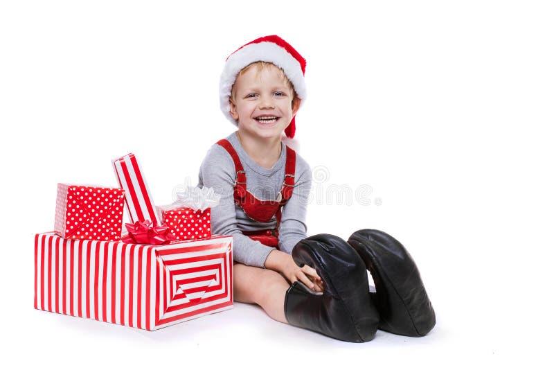 Concept: Kerstmis in kinderjaren Jong geitje in rood kostuum van dwerg met giften stock afbeelding