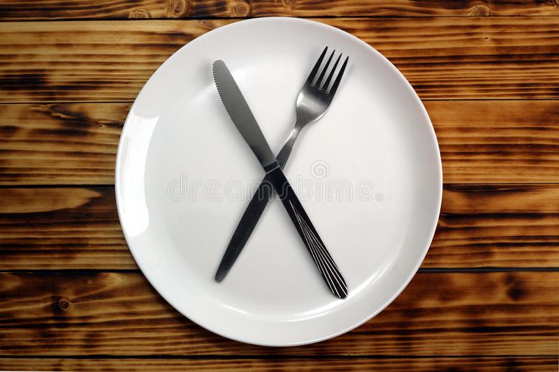 The concept of ketogenic diet, weight loss. fork and knife crossed on a white plate on a wooden table. Dishes, fork, knife, plate, white, silver, cutlery, cross royalty free stock photography