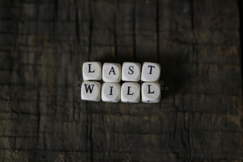 Concept last will and testament. Small wooden blocks with letters on the old worn wooden table royalty free stock photos