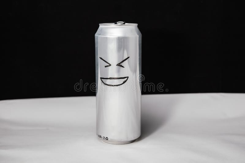 Concept of laugh man. grinning emoticon on aluminium can, Emoji with XD face. On black background.  royalty free stock image