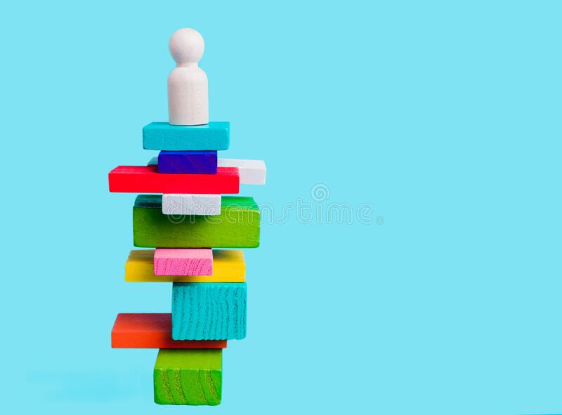 Concept of leadership, winner, creativity. Human figure on a pedestal. On colored blocks on a blue background stock images