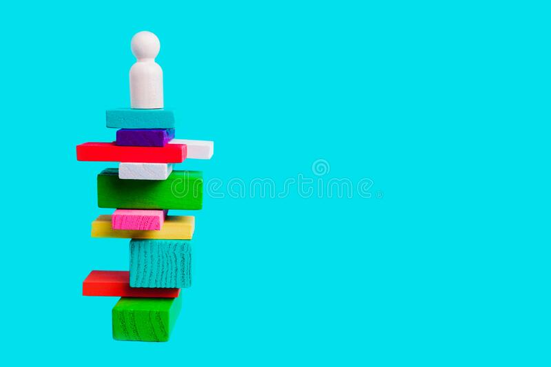 Concept of leadership, winner, creativity. Human figure on a pedestal. On colored blocks on a blue background royalty free stock image