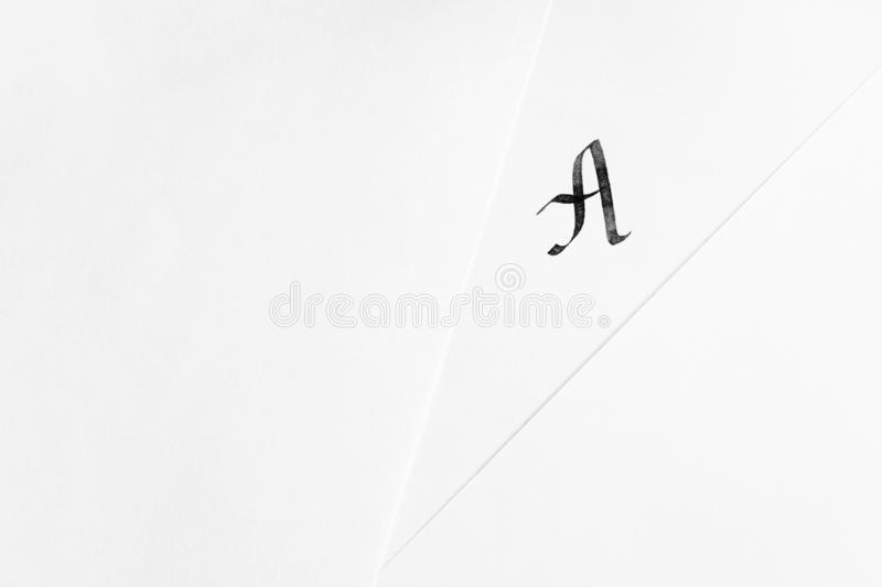 The concept of learning calligraphy, letters. Sheets of white paper with handwritten letter A. The concept of learning calligraphy, letters. Minimalism, place royalty free stock photo