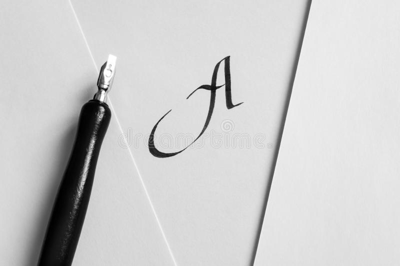The concept of learning calligraphy, letters. Sheets of white paper with handwritten letter A, next to a pen and a bottle of ink. The concept of learning stock images