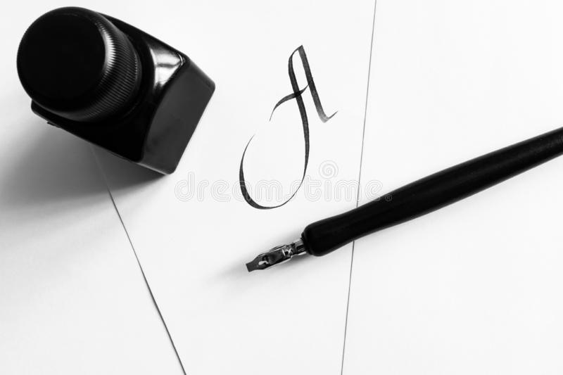 The concept of learning calligraphy, letters. Sheets of white paper with handwritten letter A, next to a pen and a bottle of ink. The concept of learning royalty free stock images