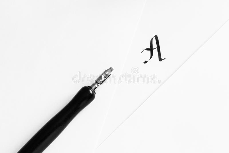 The concept of learning calligraphy, letters. Sheets of white paper with handwritten letter A, next to a pen. The concept of learning calligraphy, letters royalty free stock photos