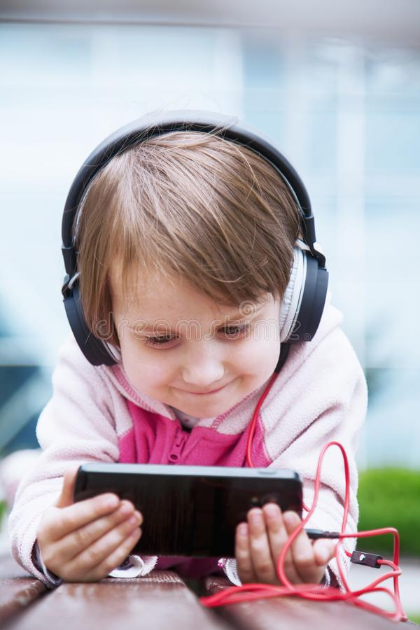 Concept: Learning is everywhere and anytime. Little child girl using mobile phone watching online e-learning video to studying stock images