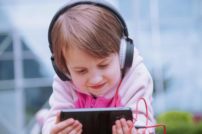 Concept: Learning is everywhere and anytime. Little cute child girl using mobile phone watching online e-learning video to stock images