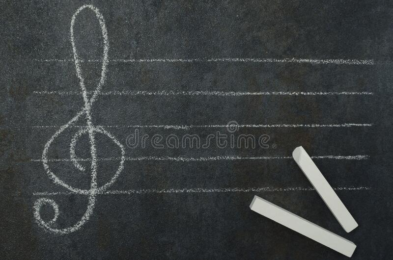Concept of learning how to compose music. G-clef, empty staff and piece of chalk on the chalkboard. Top view of g-clef and earphones as symbol of notes on the royalty free stock photos