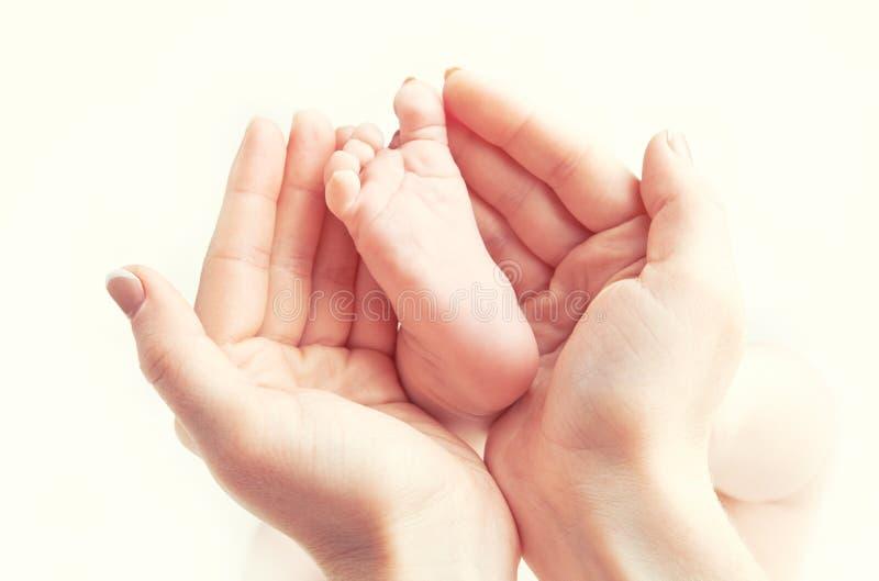 Concept liefde, ouderschap, moederschap pasgeboren babyvoet in mo stock afbeeldingen