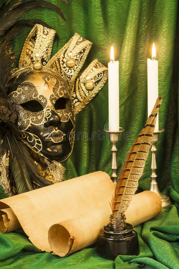 Literature concept, candle in a candlestick near a Venetian mask royalty free stock photos