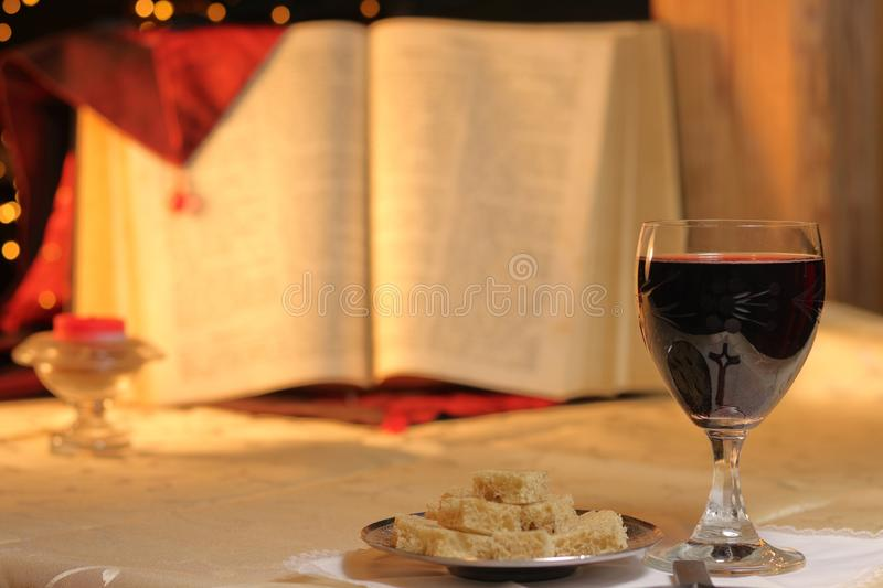 Concept Lord`s Supper and Christian communion. Bread and wine in chalice are front of big Bible. Cross reflect in goblet, candle stock photo