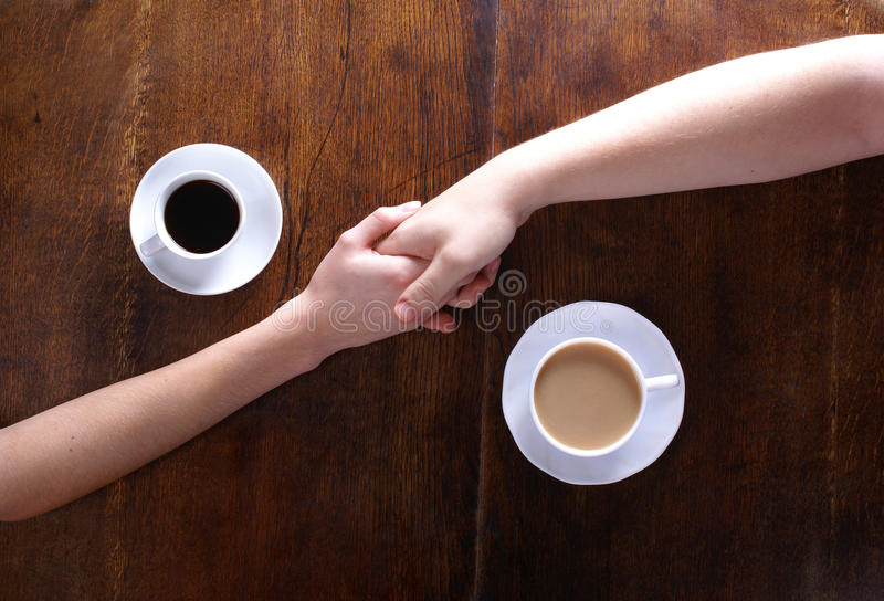 Concept of love and coffee. Concept of male and female hands, love and coffee. Composition taken on a brown wooden table stock photo