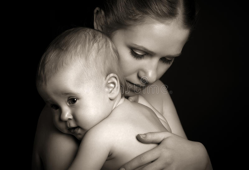 Concept for love and family. mother hugging baby tenderly in mon stock images