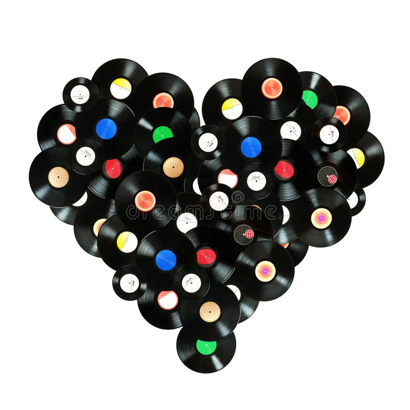Concept We love music. Colorful heart shape made of vintage vinyl records, isolated over white background, all labels designed by myself royalty free stock photos