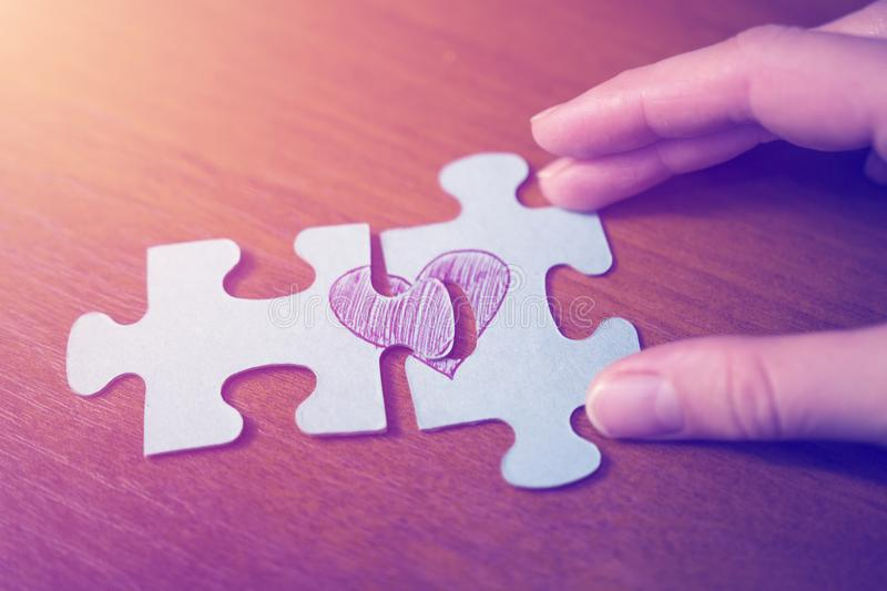 The concept of love. Puzzles of the heart. Hands connect the two halves of the heart royalty free stock photos