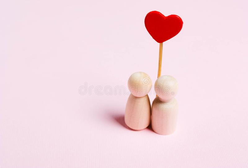 The concept of love, romance.Figurines of a woman and a man with a heart stock photo