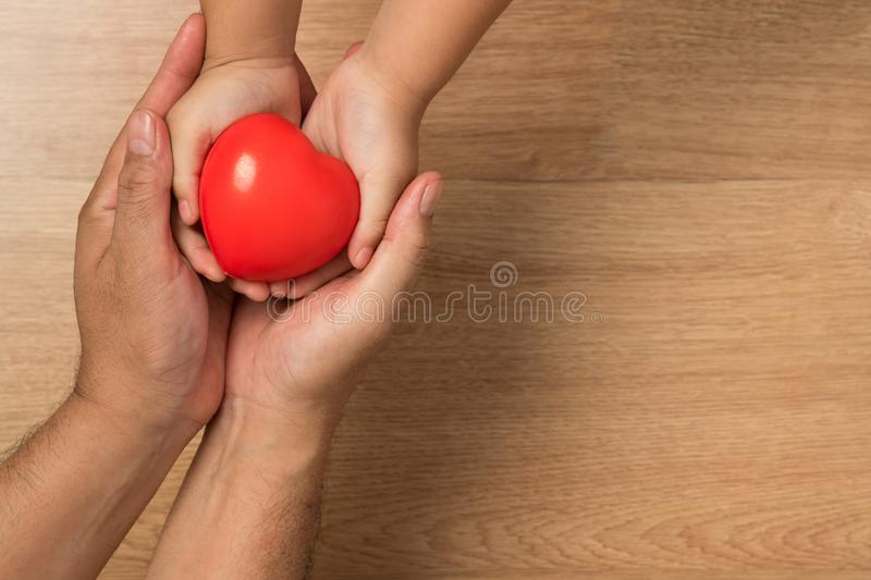 Concept of love in Valentine`s Day. Man hands carries red heart stock photo