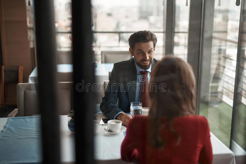Young man and woman having meeting in restaurant. Concept of lovely date. Selective focus on cheerful gentleman sitting in restaurant with young lady in red royalty free stock images