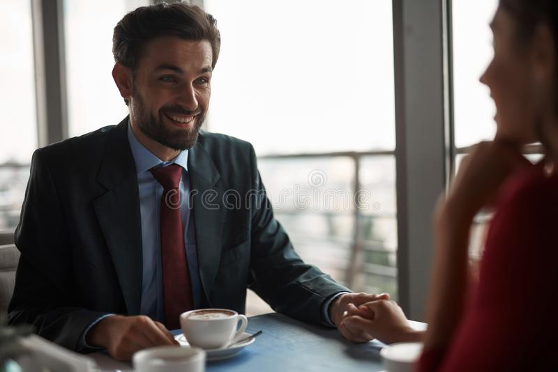 Smiling man and woman having meeting in restaurant. Concept of lovely date. Selective focus on cheerful gentleman tenderly holding hand of young lady in red royalty free stock photos