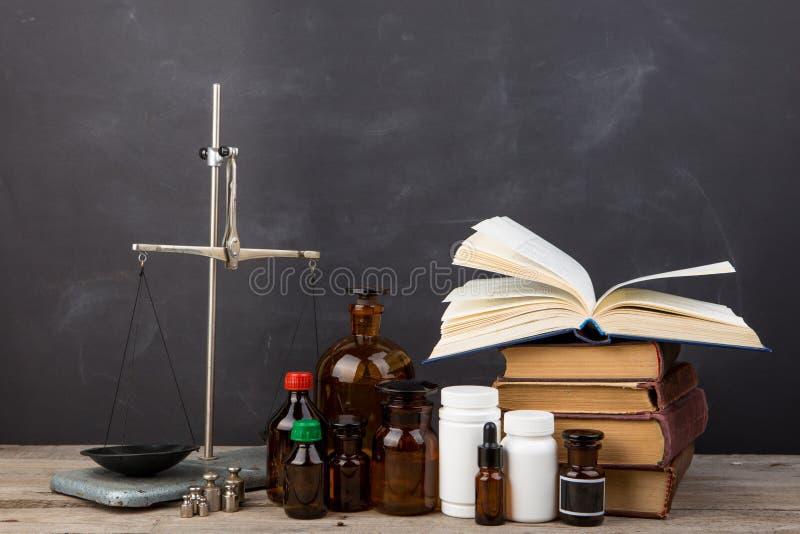 Concept médical d'éducation - livres, bouteilles de pharmacie, stéthoscope dans l'amphithéâtre avec le tableau noir photos libres de droits