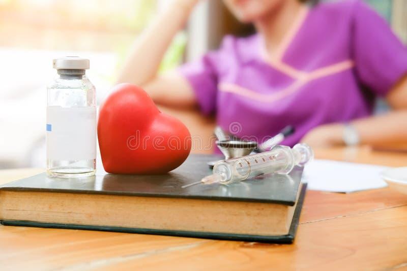 Concept médical de maladie cardiaque de recherches, livre modèle, seringue et bouteille de coeur de médecine sur la table photo stock