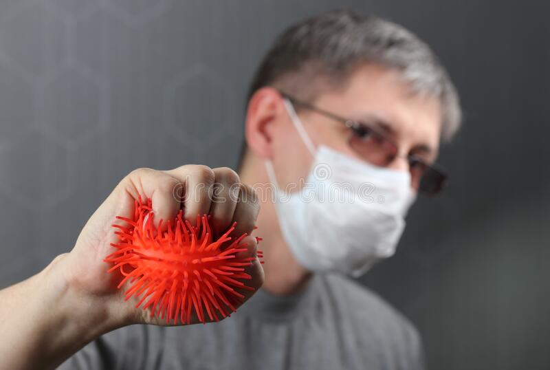 The concept, a man in a medical mask on his face, makes a barrier to the spread and does not allow the virus. Epidemic, Coronavirus stock photos