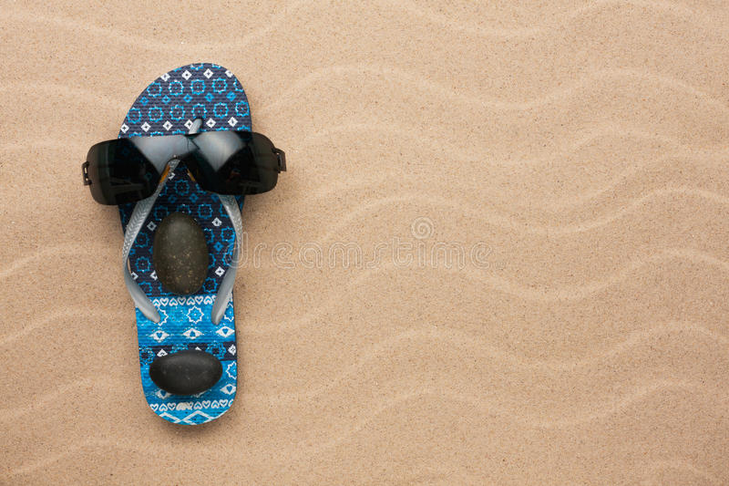 Concept of a man's face, flip-flops and sunglasses. On wavy in sand stock image