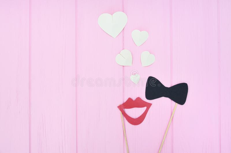 Concept of man and woman fallen in love. Female lips and bow-tie with hearts on a pink wooden background with place for royalty free stock image