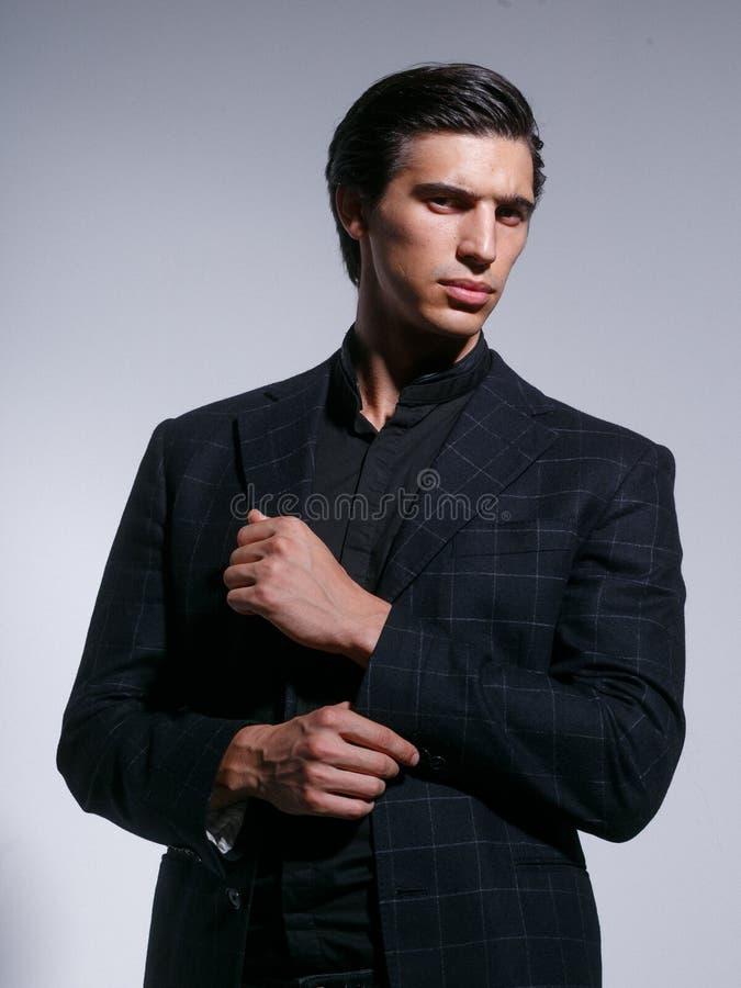 Concept masculin de beaut? Homme bel de brune gardant son bouton sur le bras, d'isolement sur un fond blanc photographie stock