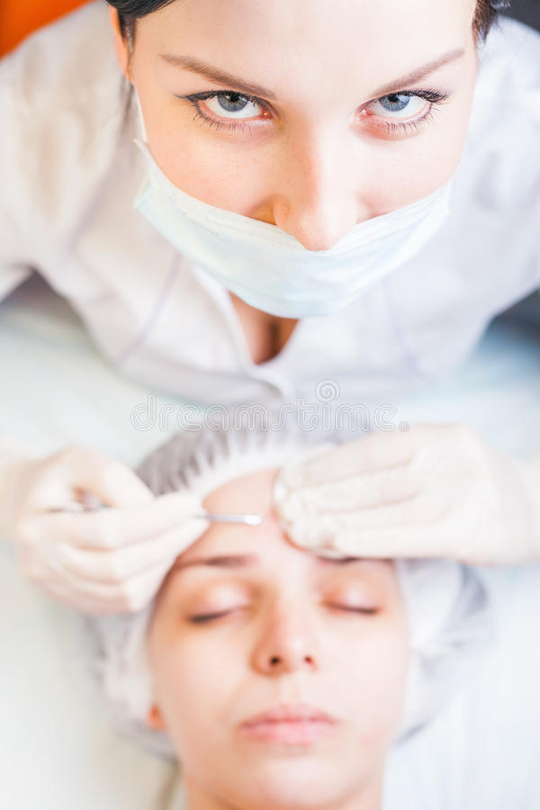 Concept of medical treatment of rejuvenation and skincare. Cosmetologist and patient at spa beauty salon looking up at camera, before acne treatment, holding stock image