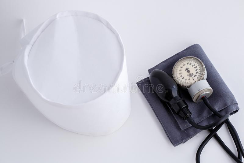 Concept for medicine. Medical items medical cap, tonometer, stethoscope on a white isolated background.  royalty free stock photos