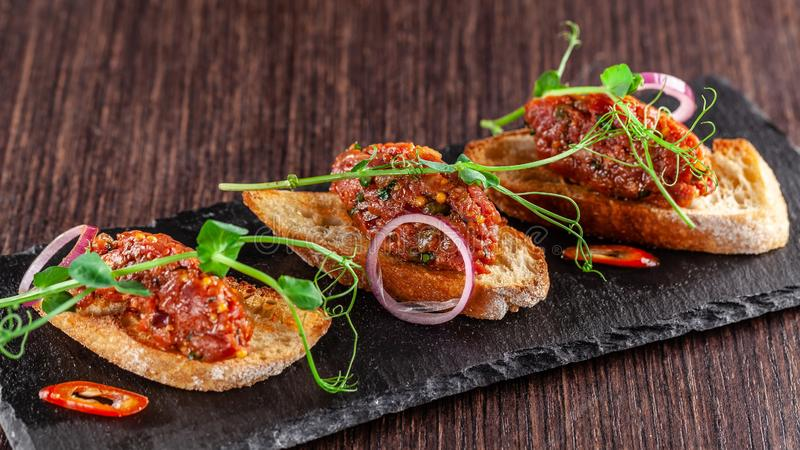 The concept of Mexican cuisine. Beef tartare with parsley, French mustard beans on baguette croutons. A dish in the restaurant. On a black stone slate royalty free stock photo