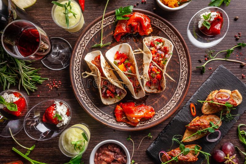 The concept of Mexican cuisine. Mexican food and snacks on a wooden table. Taco, sorbet, tartar, glass and bottle of red wine. Background image. Top view, copy stock image