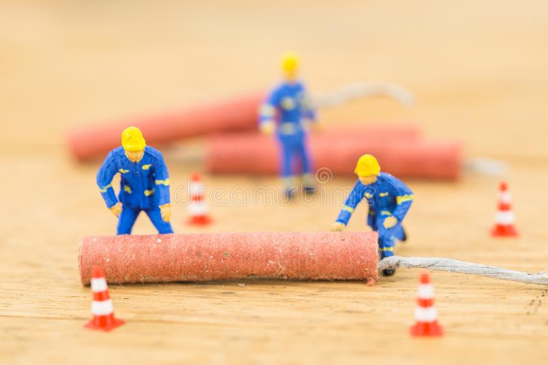 Concept miniature people working on Firecracker. Concept miniature people working Firecracker royalty free stock photo