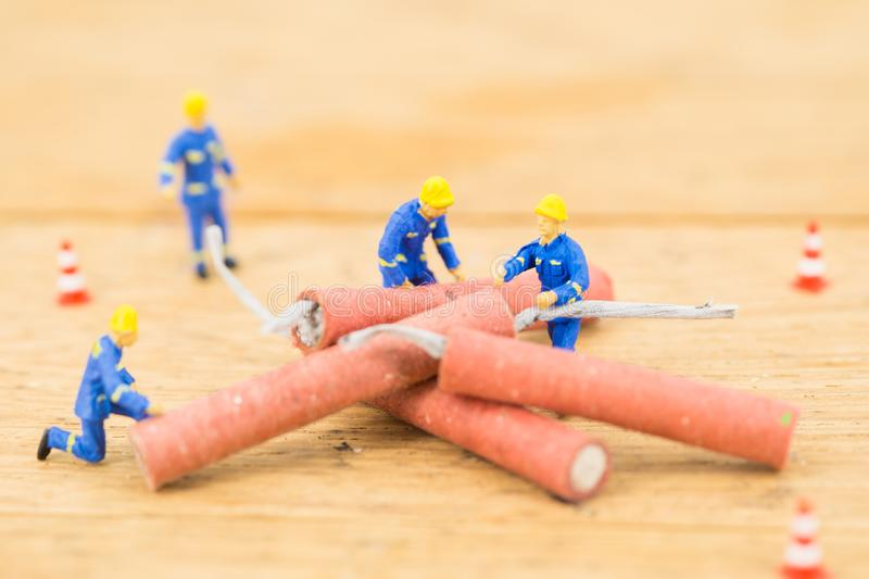 Concept miniature people working on Firecracker. Concept miniature people working Firecracker royalty free stock photography