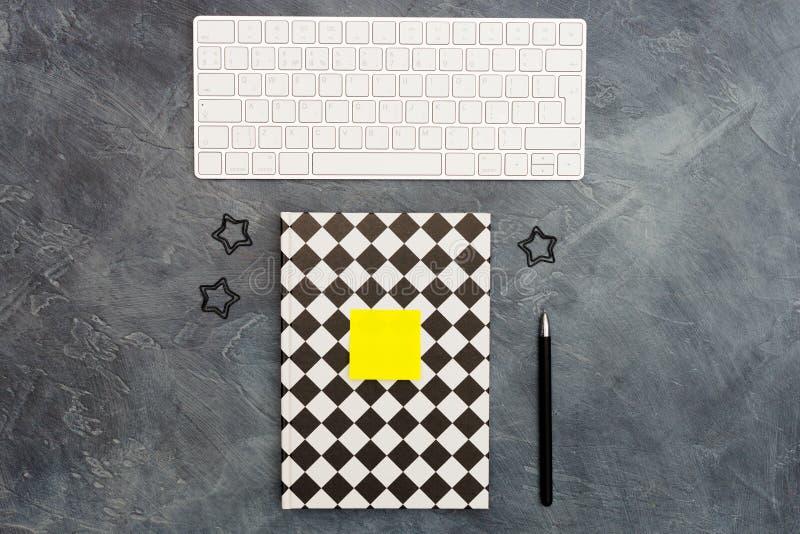 Concept minimal de bureau Clavier, trombones de manque, note et stylo collant jaune lumineux et blanc noir ferm? color images libres de droits