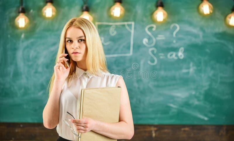 Concept mobile de rapport Femme avec le livre parlant au téléphone portable dans la salle de classe Professeur sur la solution co image stock