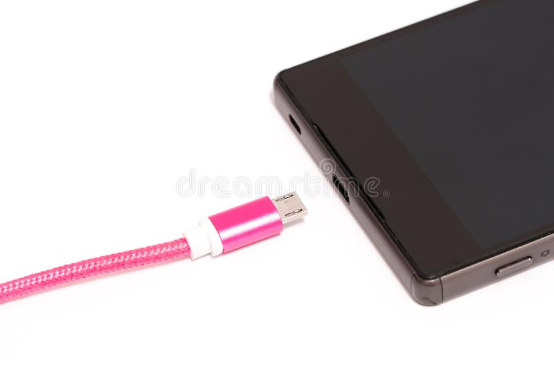 Concept of mobile phone charging. Pink micro usb cord near smartphone power plug. Isolated on white stock photo