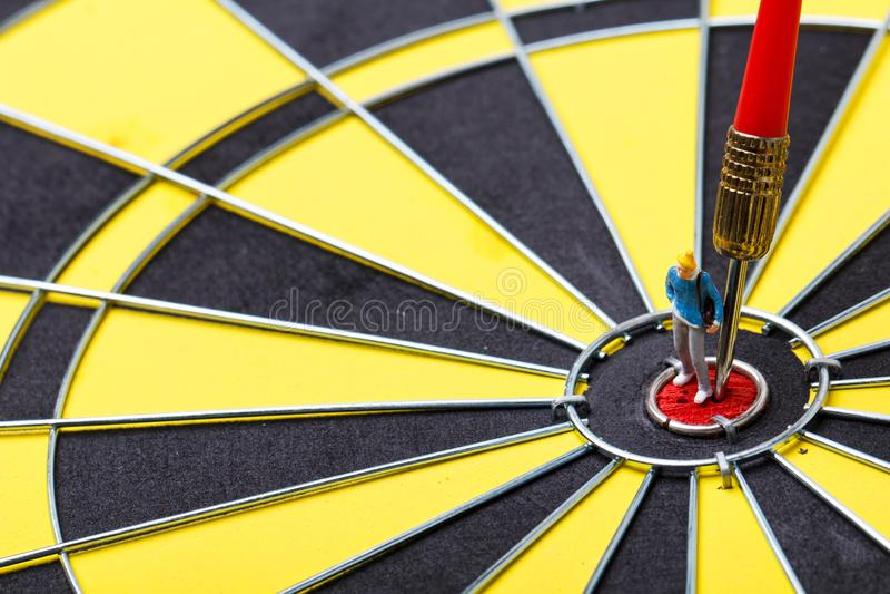 Model mini people walks towards the target on dart board. stock image