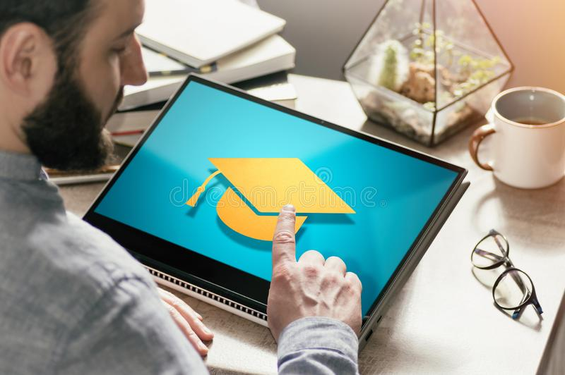 Concept of modern technology in education. Image. Bearded man with laptop at his desk. He presses on the graduation hat icon. Concept of modern technology in royalty free stock images