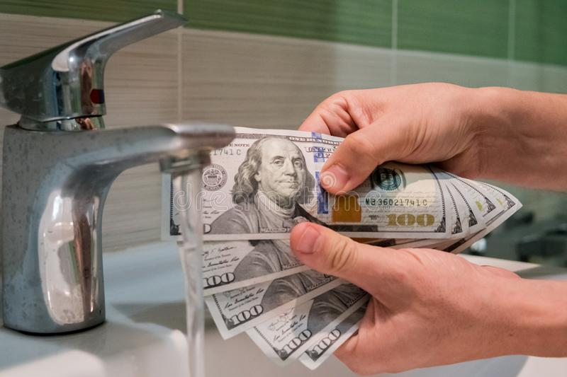 Concept of money laundering. Banknotes of 100 dollars in the hands of men near water jets in washbasin stock photography