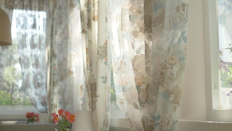 The concept of morning. beautiful curtains with a floral print are waving in the wind from a half-open window. sun glare royalty free illustration