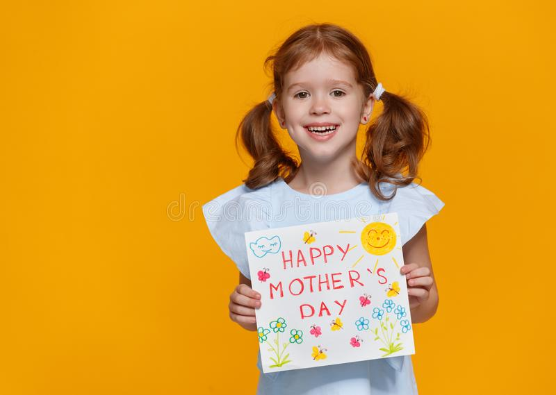 Concept of mother`s day. cheerful laughing child girl with postc. Concept of mother`s day. cheerful laughing child girl with picture postcard on colored stock images