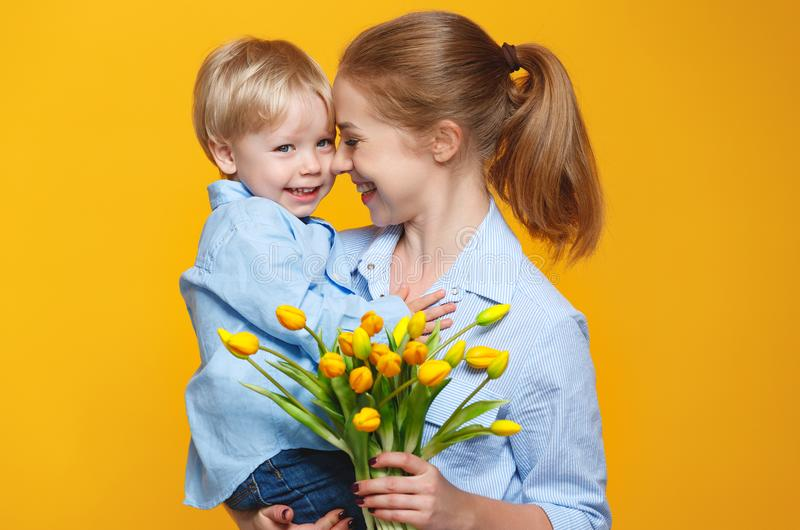 Concept of mother`s day. mom and baby son with flower on colored stock photo