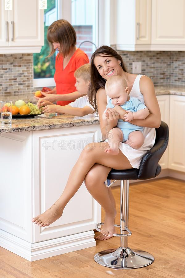 The concept of motherhood, nanny, infancy and childhood. Indoor shot in the kitchen. Two women and a baby in their arms, looking stock images